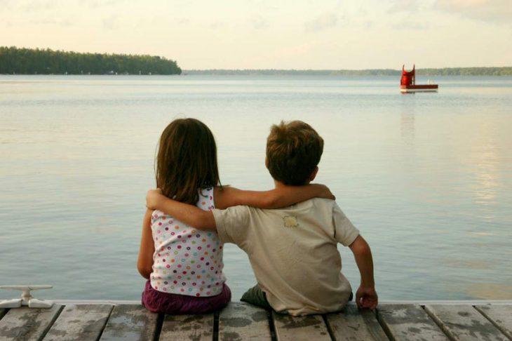 niño y niña abrazados en un muelle de espaldas