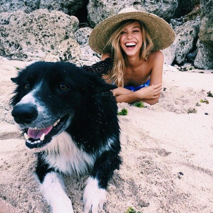 perro y muer acostada en la playa sonriendo