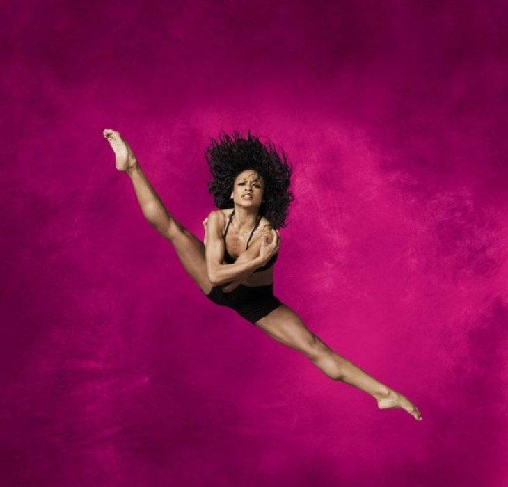 bailarina profesional salto y piernas abiertas afro rosa