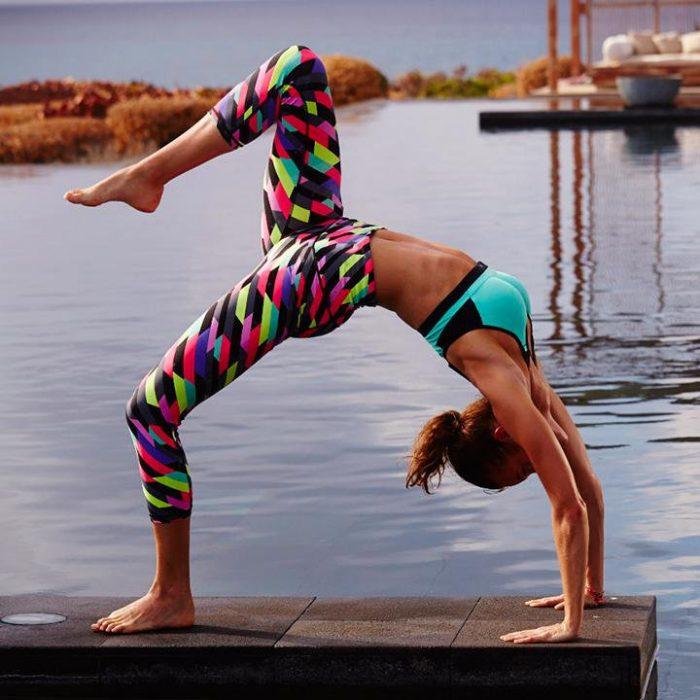 mujer haciendo yoga y pose en muelle lago