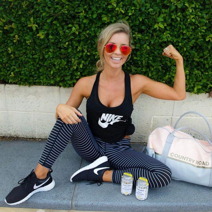 mujer fitness sentada en el suelo sonrie