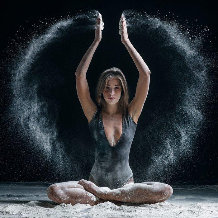 mujer sentada con brazos hacia arriba y arena