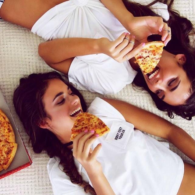 mujeres acostadas comiendo pizza sonríen