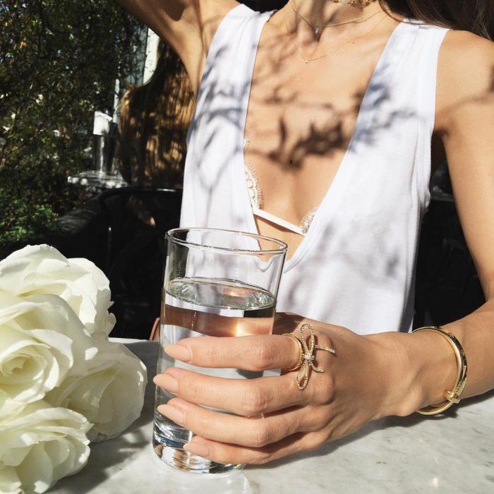 mujer sentada con un vaso de agua en la mano