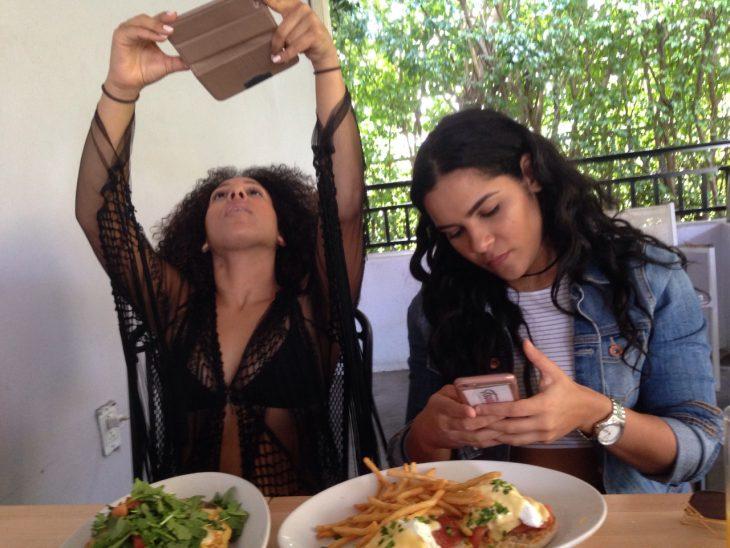 dos mujeres tomandole fotos a la comida