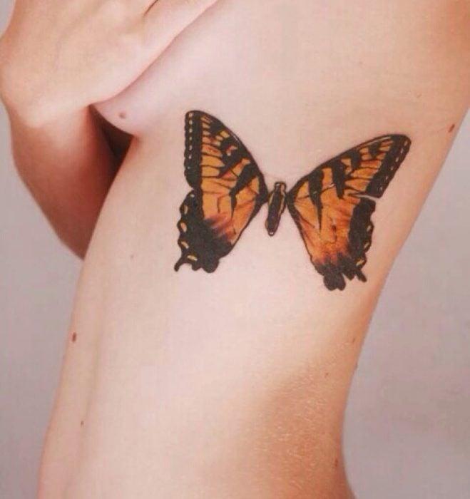 tatuaje de mariposa monarca en las costillas