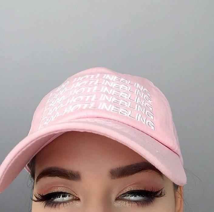 mujer con gorra rosa pastel rueda los ojos