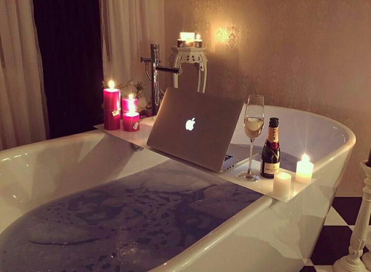 tina de baño con vino, velas y computadora