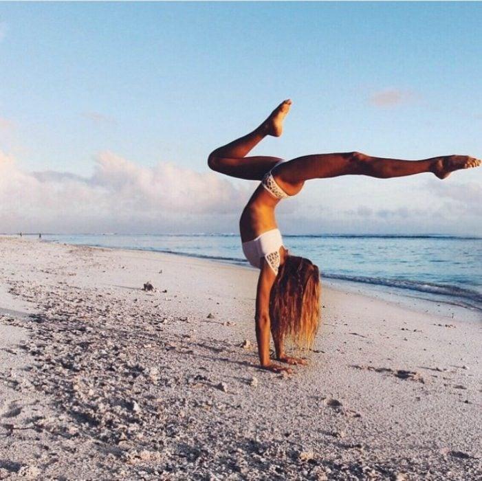 mujer haciendo yoga en la playa