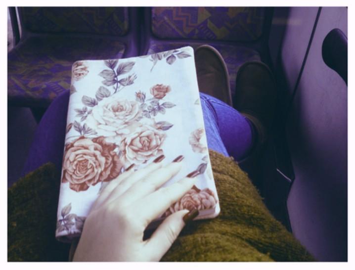libro forrado de papel de flores en las manos de una chica con uñas rojas