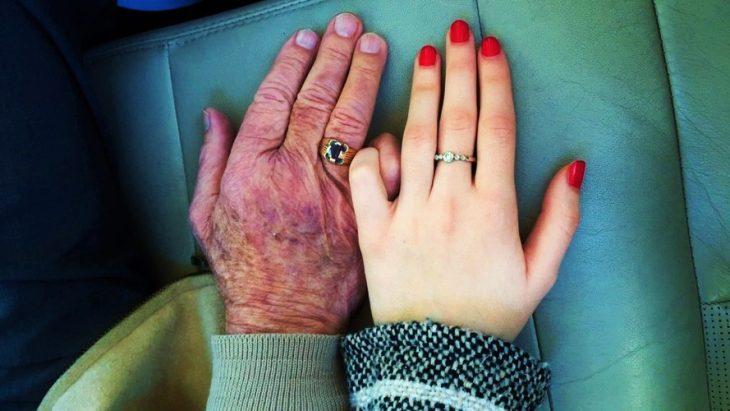 manos de abuelo y de nieta anillos y uñas rojas