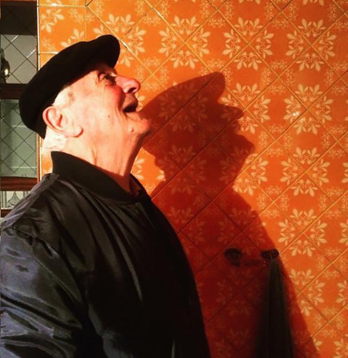 abuelo sonríe feliz de perfil pared naranja