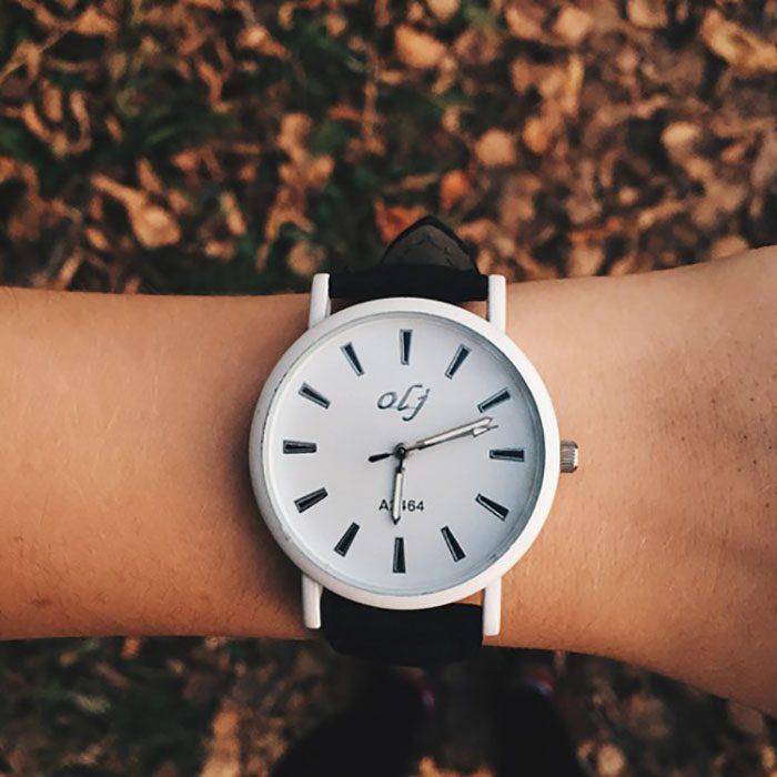 mano con reloj de mano y hojas de otoño