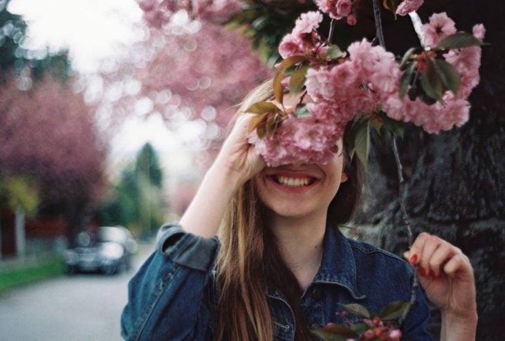 chica sonrie detras de flores rosas