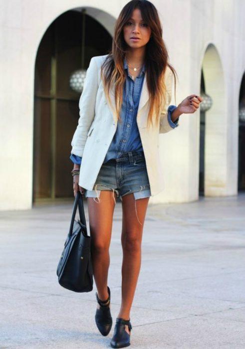 mujre con shorts de mezclilla bolsa y blazer saco blanco
