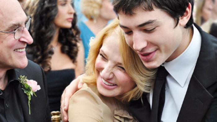 mujer rubia sonriendo y abrazando a su hijo