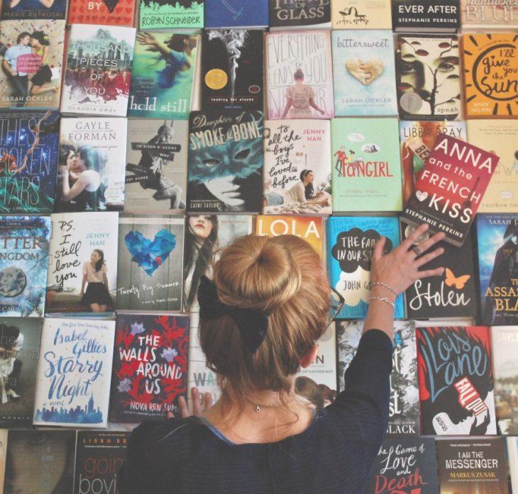 chica rubia con chongo acomodando libros