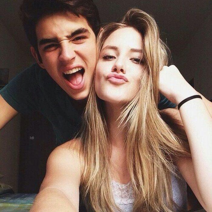 pareja feliz sonríe y mujer manda beso