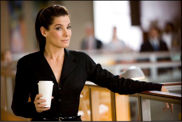 Escena de la película la propuesta chica con un café mirando intensamente a las personas