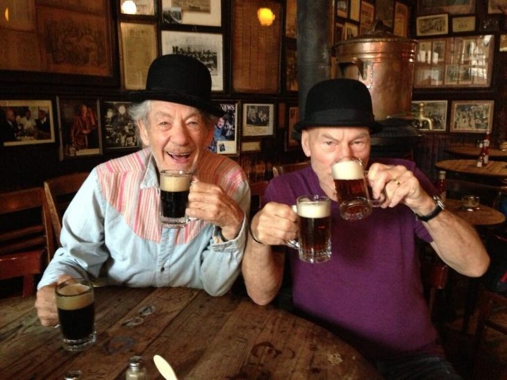 dos hombres mayores con sombrero y cerveza en bar