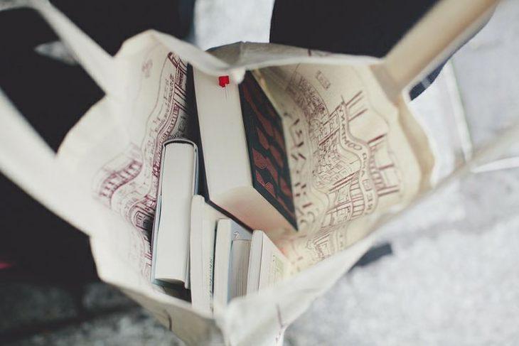 bolso blanco abierto con tres libros