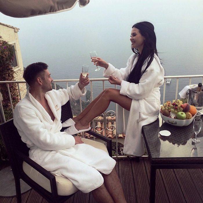 pareja en balcon con bata y copas de vino