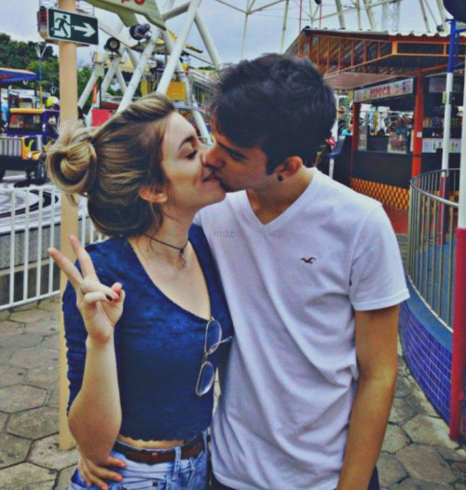 pareja en parque de diversiones chica señal de amor y paz
