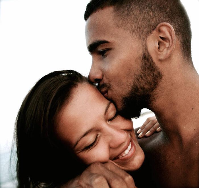 mujer sonrie y hombre le da beso en la cien