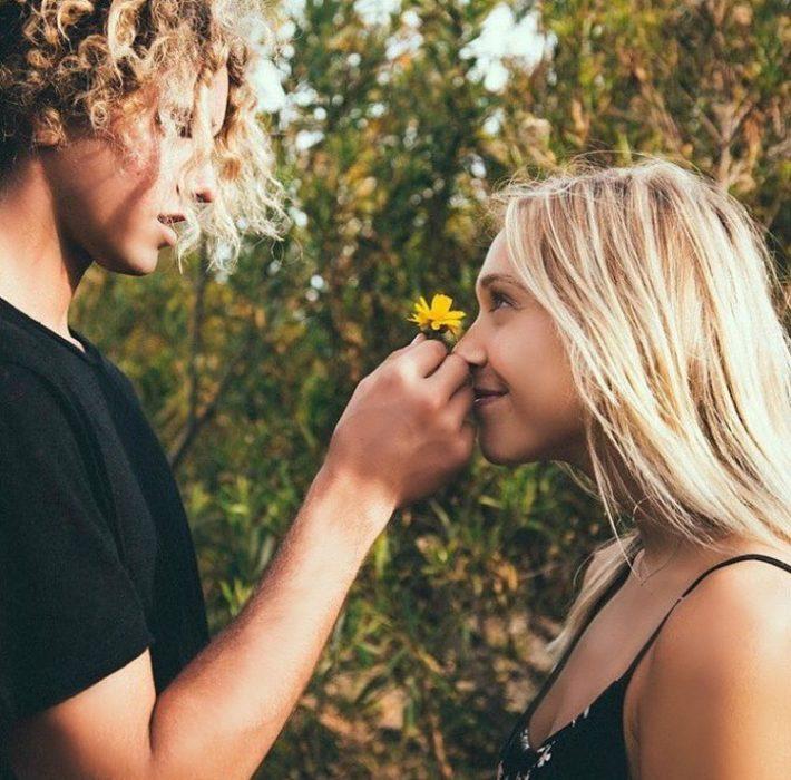 hombre y mujer de frente chico le pone flor en la nariz