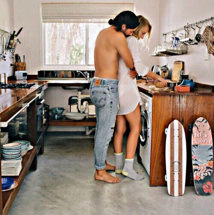 hombre abraza a mujer por detrás en la cocina