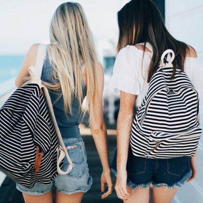 mujeres de espalda con mochila de rayas