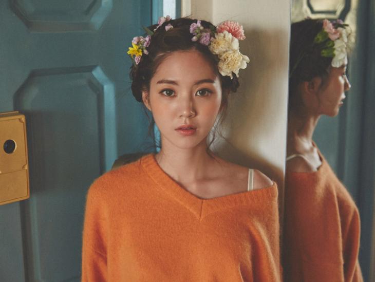 chica asiatica con corona de flores y sueter naranja