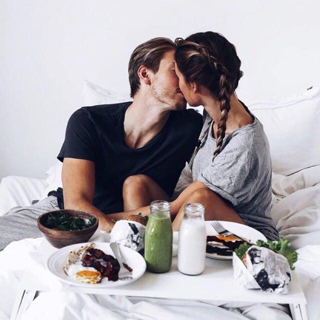 pareja dandose un beso en la cama desayunando