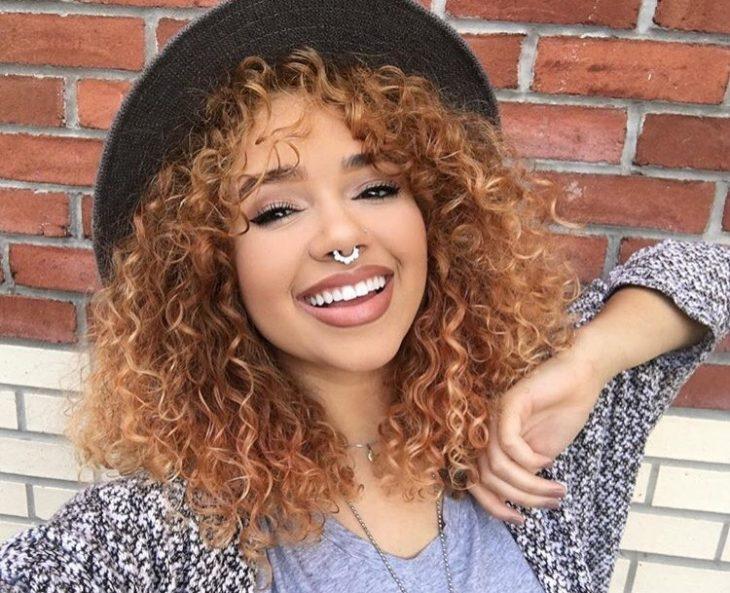 chica de cabello rizado y sombrero sonrie