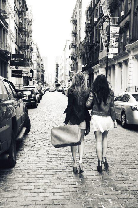 Chica con una maleta en la mano viajando junto a su mejor amiga