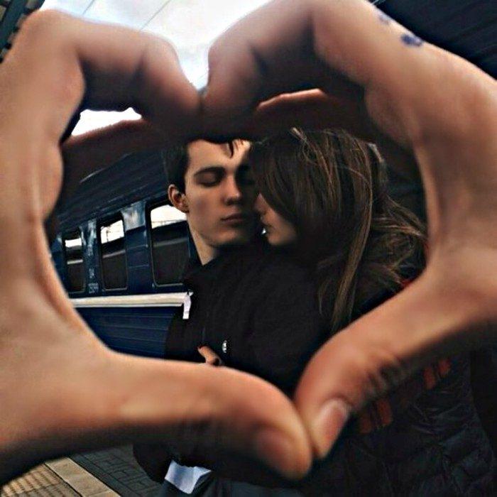 pareja se da beso y detrás de un corazón