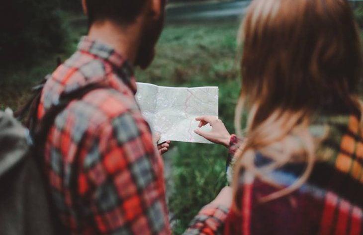 pareja mirando un mapa en el bosque