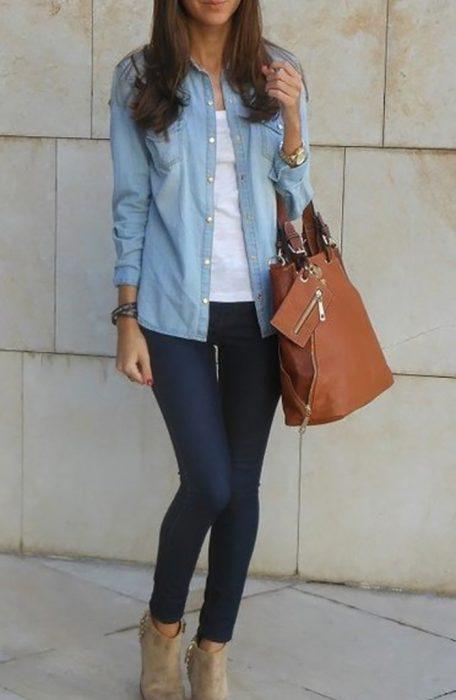 chica con pantalon y camisa de mezclilla y bolso cafe