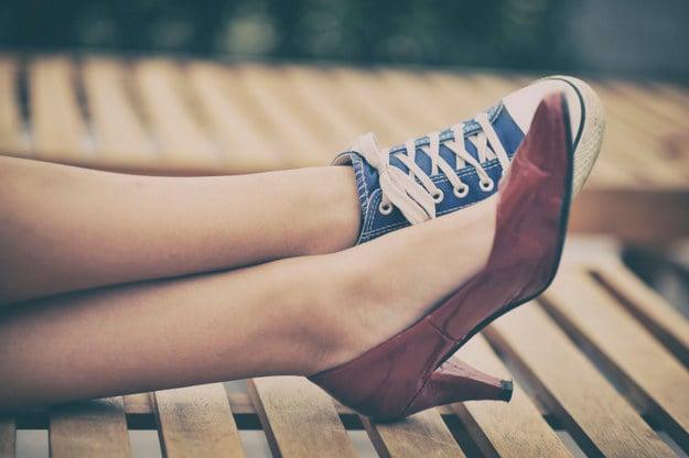 chica con un tennis y un zapato de tacón