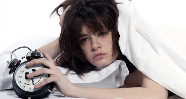 chica despierta y cansada con despertador en mano