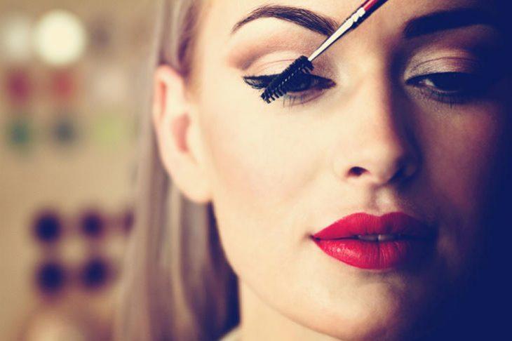 mujer es maquillada y le aplican rimel con cepillo delgado