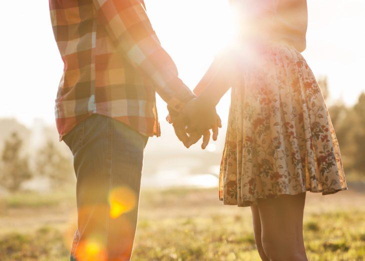 pareja tomados de la mano en el campo