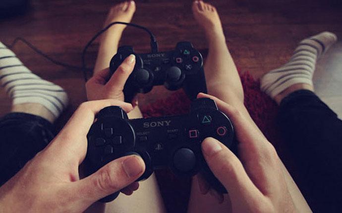 manos de pareja jugando videojuegos