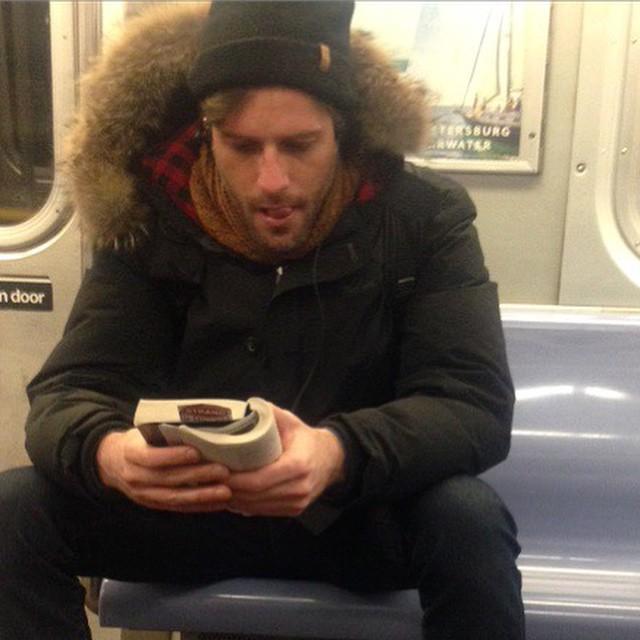 hombre de gorra y chamarra leyendo un libro