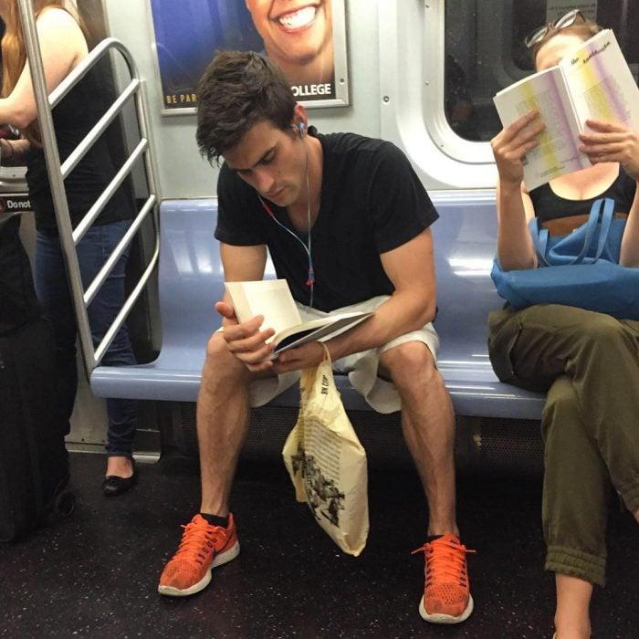 hombre sentado de playera blanca leyendo un libro