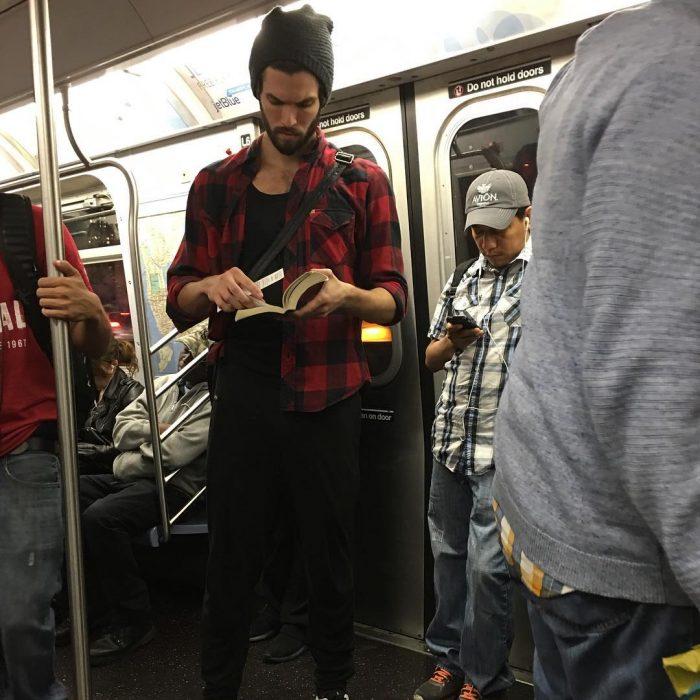 hombre de gorra y camisa de cuadros leyendo un libro