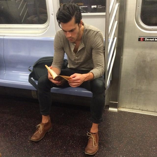 hombre de playera gris leyendo un libro en el metro