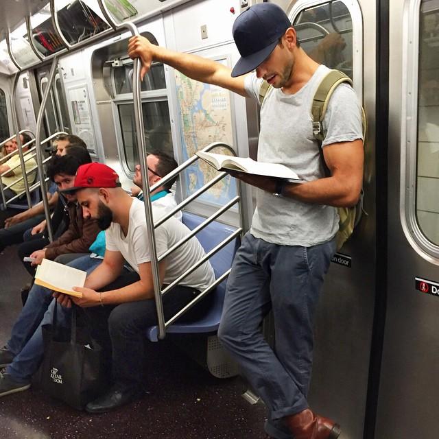 hombre de gorra azul leyendo libro en el metro