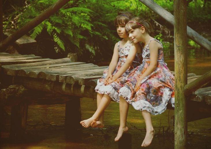 dos niñas sentadas en un muelle se abrazan