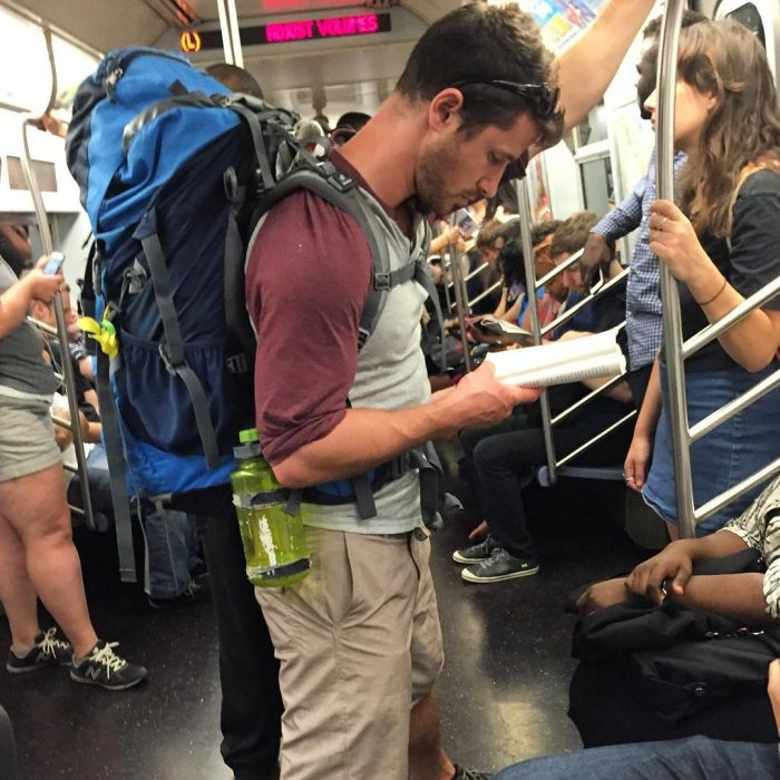 hombre con mochila azul leyendo un libro